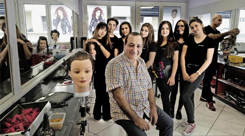 Le coiffeur Resul Açikalin entouré de ses élèves à l'Académie de coiffure de la rue de Carouge.© Steeve Iuncker-Gomez