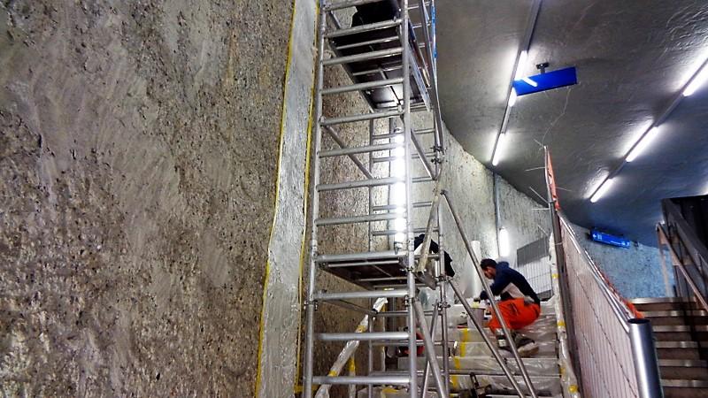 12. Des ouvriers colmatant des fissures au-dessus des escaliers