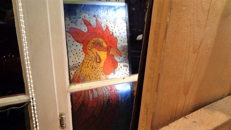 11. Un coq en pyrogravure et peinture se reflète dans la vitrine