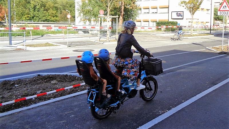 Cycliste avec deux enfants à l'arrière… On croise les doigts…