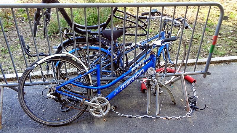 Une barrière avec des carcasses de vieux vélos enchaînés